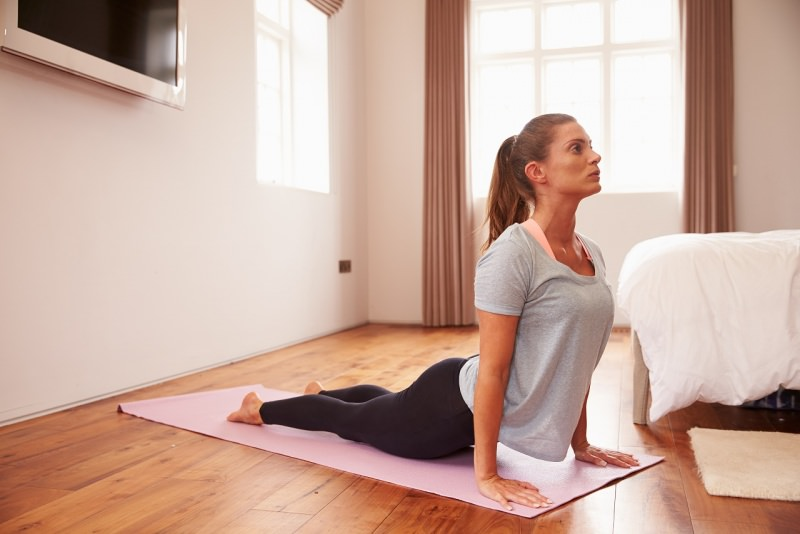 donna fa stretching addominali su tappeto resto a casa