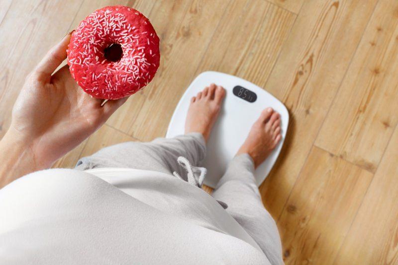 donna sovrappaeso su bilancia obesità ciambella dolce