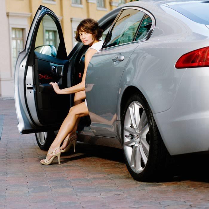 Guidi coi tacchi? Scegli tappetini per auto in gomma bella donna al volante auto grigia capelli corti castano ramato abito bianco sandali beige tacco alto guidare sicurezza