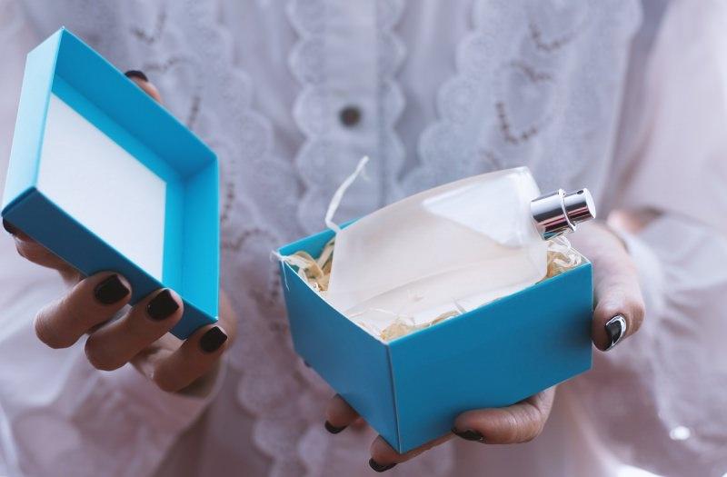 mani di donna tengono scatola azzurra con bottiglia profumo spray