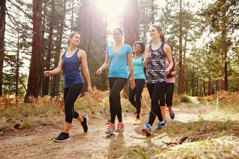 giovani donne passeggiano camminando fitness fitwalking foresta alberi