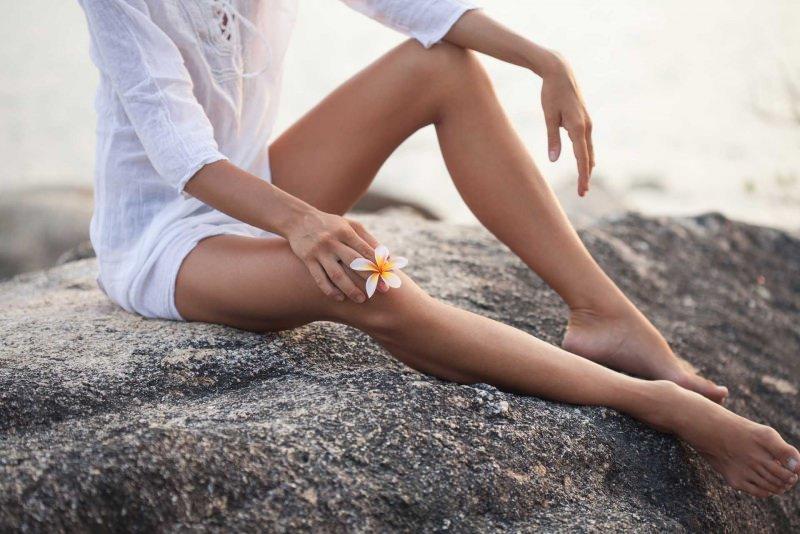 Epilazione totale: funziona davvero corpo donna blusa bianca lino pelle liscia depilata gambe fiore bianco giallo scoglio mare