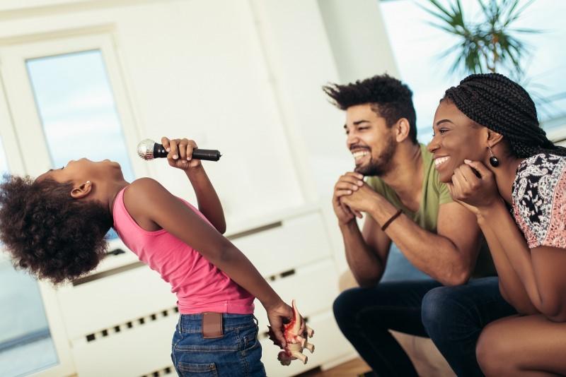 papà e mamma guardano la figlia con microfono canta karaoke