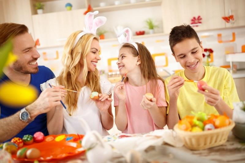 famiglia dipinge uova pasquali mamma papà figlio figlia orecchie coniglietto cucina