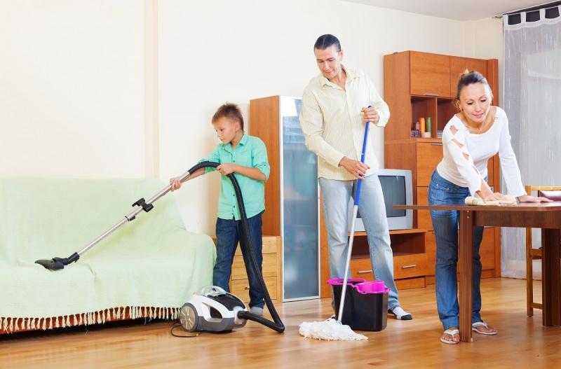 famiglia fa le pulizie di primavera in casa mamma papà figlio