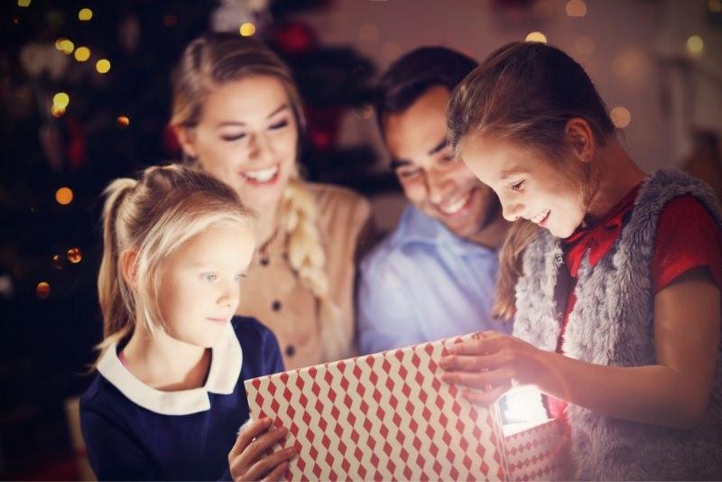 famiglia felice mamma papà figlia figlio sorridono mentre aprono regali di Natale davanti albero luci