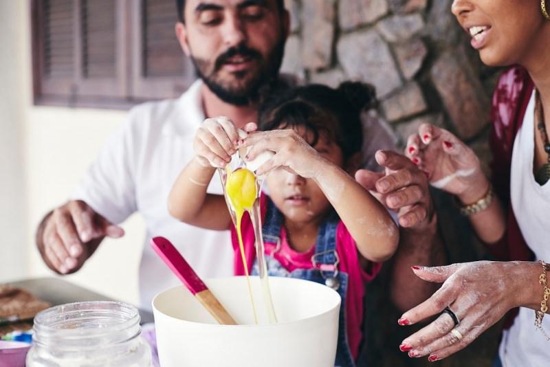 famiglia felice papà e mamma aiutano figlio bambino a cucinare