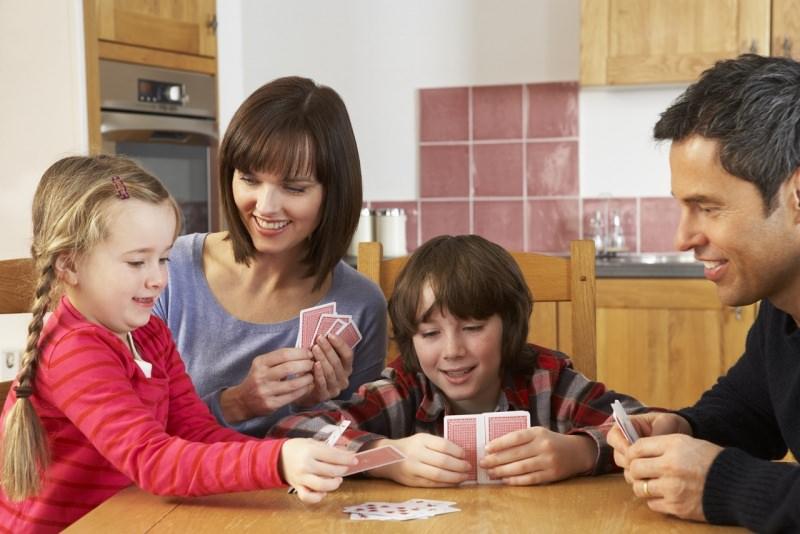 famiglia felice bambini gioca a carte in cucina