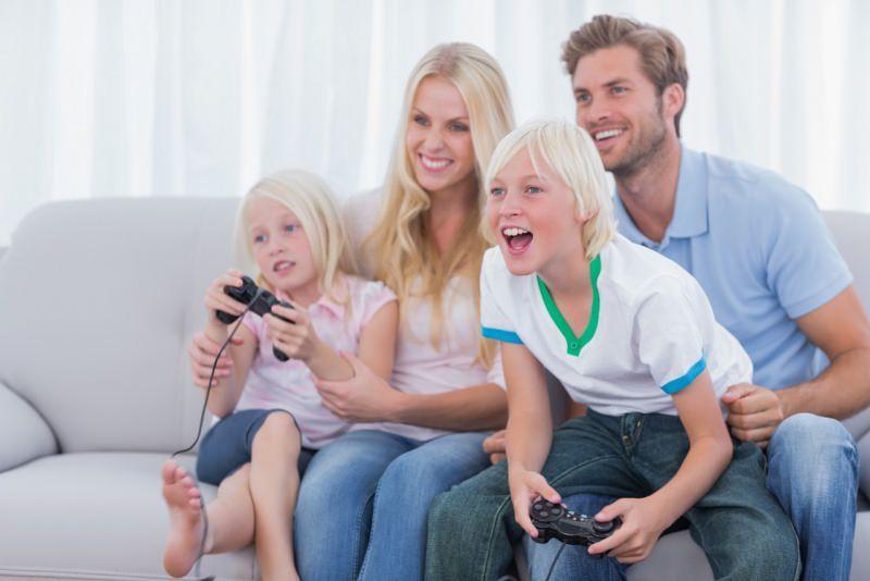 famiglia felice con bambini gioca video giochi a casa in soggiorno