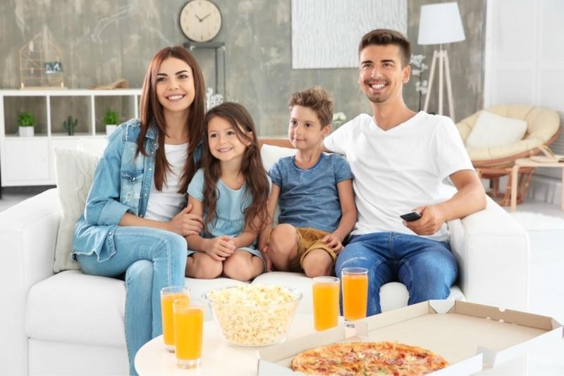 famiglia felice mamma papà figli sorrisi guardano tv mangiano pizza popcorn bicchieri succo arancia
