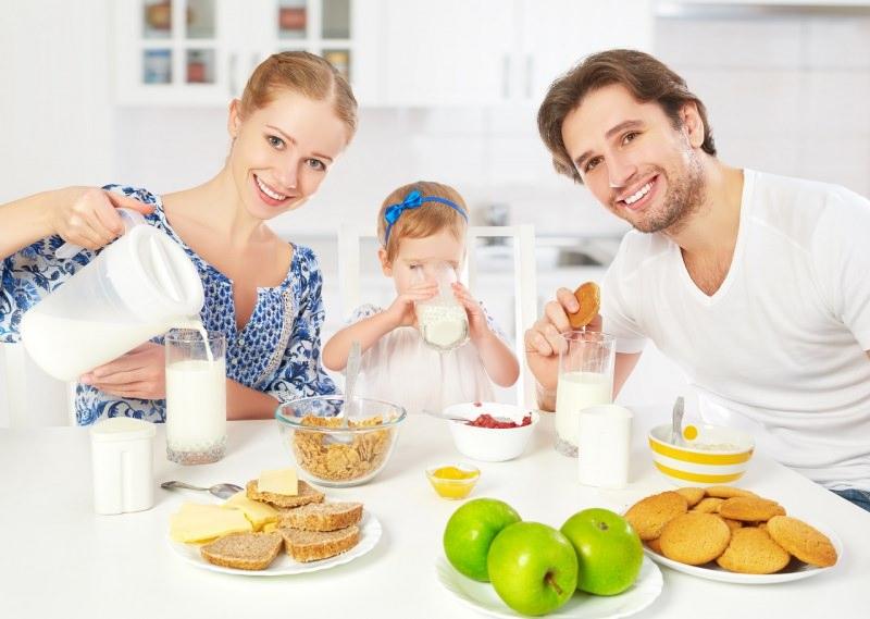 famiglia felice giovane donna capelli biondi sorrisi mamma bambina piccola figlia beve latte uomo papà biscotti latte