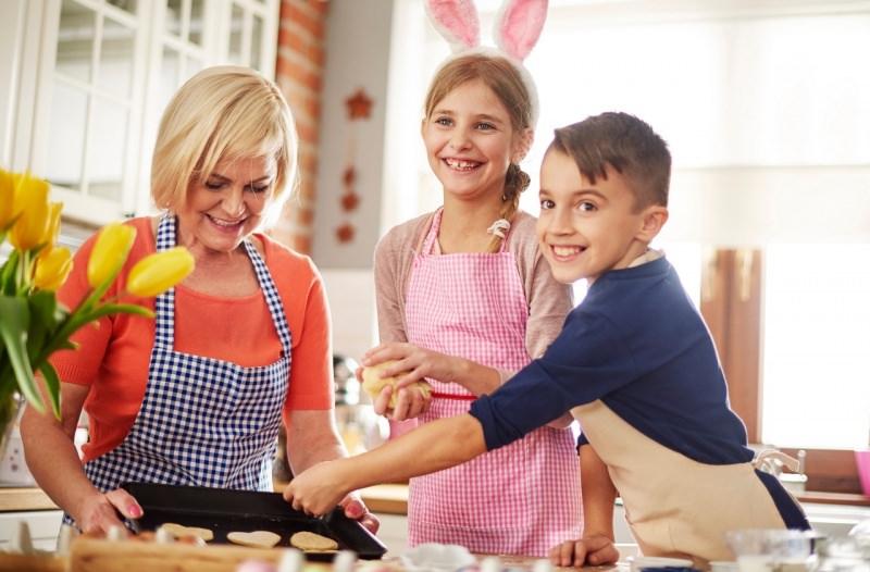 mamma e figli cucinano insieme felici periodo di Pasqua biscotti