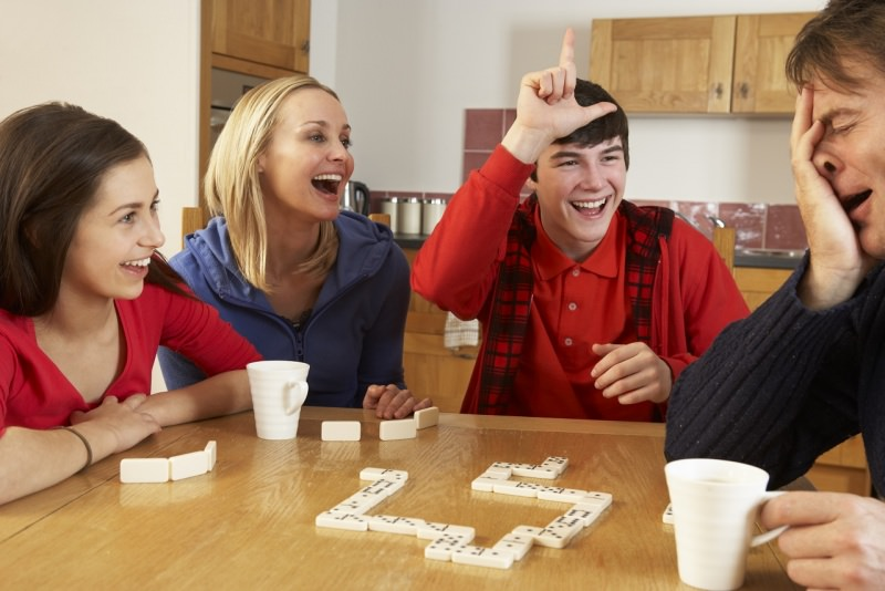 famiglia gioca a domino in cucina a casa