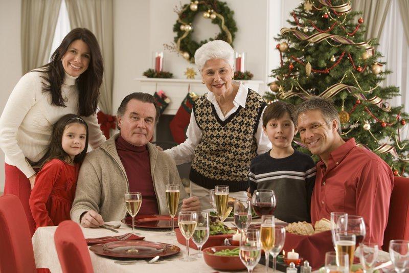 famiglia riunita tre generazioni attorno a tavola apparecchiata a festa albero di natale sorrisi