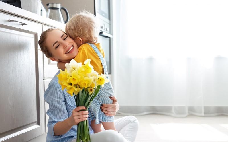 bambino biondo abbraccio mamma auguri festa della mamma fiori narcisi bianco giallo