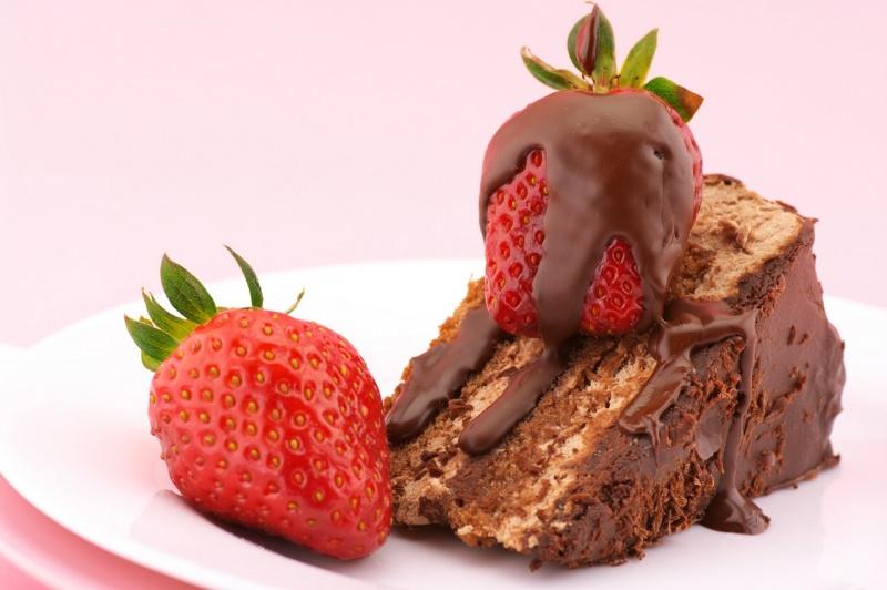 fetta di torta al cioccolato con fragola fresca ricoperta di ganache