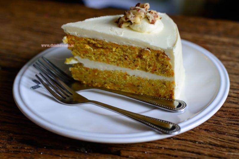 fetta di torta di carote e noci con crema al mascarpone piatto bianco forchette