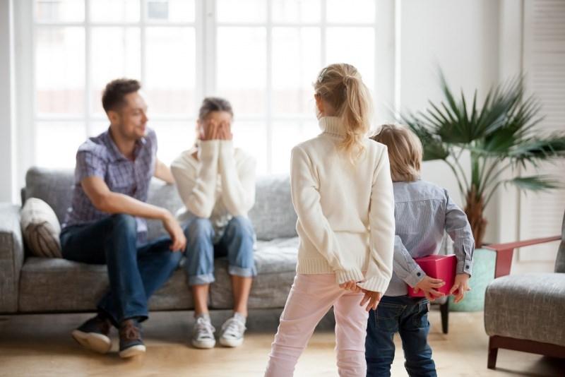 figli bambino bambina regalo sorpresa festa della mamma seduta divano papà soggiorno