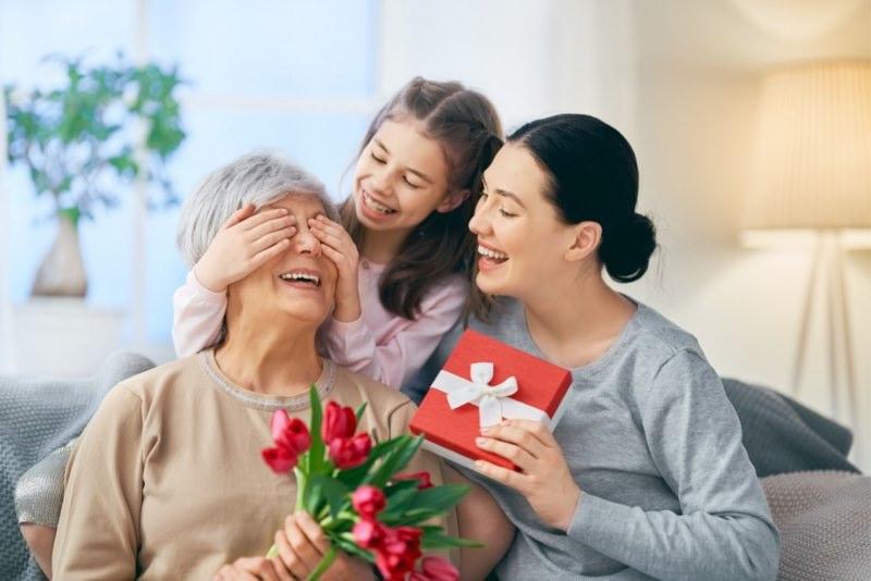 donna figlia adulta fa regalo mamma anziana bambina nipote pacco regalo fiori tulipani rossi