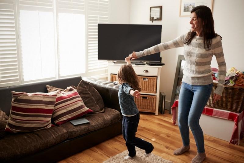 mamma e figlia ballano in soggiorno a casa tv divano