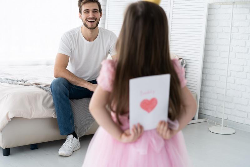 bambina regala biglietto auguri con cuore festa del papà sorriso