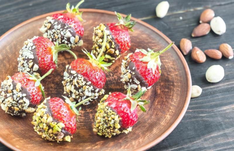 vassoio con fragole fresche ricoperte con cioccolato fondente e granella di mandorle e nocciole