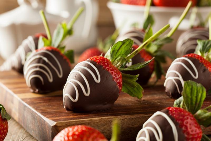 fragole fresche ricoperte con cioccolato fondente decorato bianco