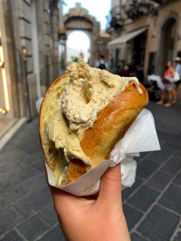 brioscia siciliana brioche con gelato in mano a una donna in strada