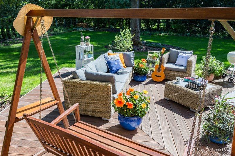 giardino accogliente divani poltrona altalena fiori chitarra cappello paglia