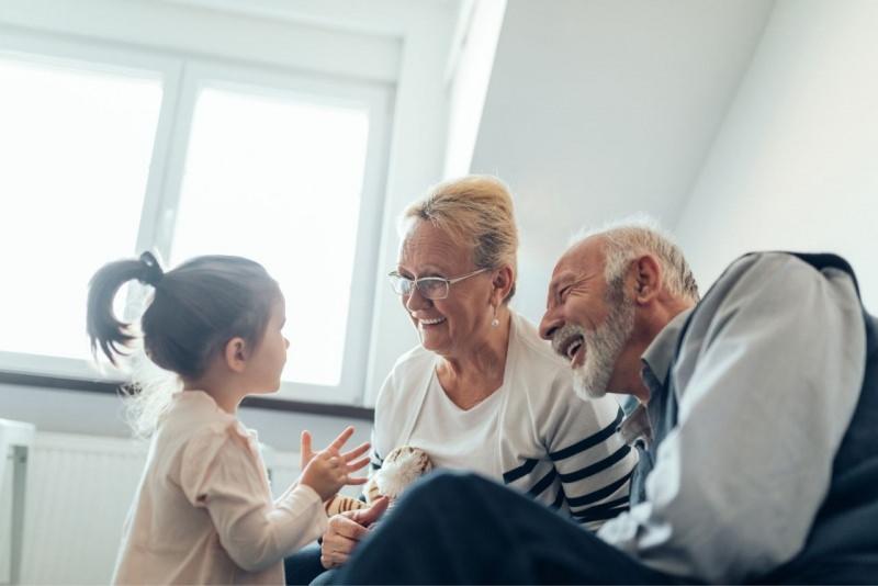 nonni sorridento ascoltano la nipotina loro gioia