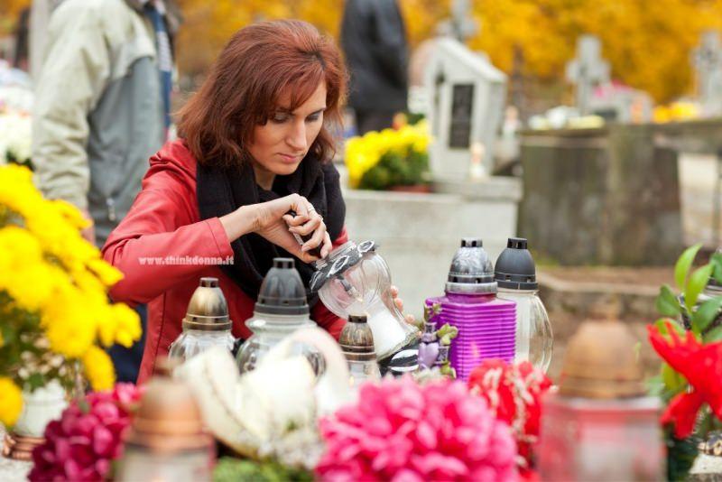 commemorazione defunti 2 novembre cimitero donna accende candela fiori crisantemi