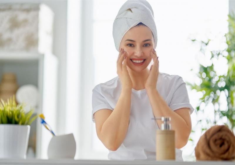 viso donna sorridente che applica crema sul viso guardandosi allo specchio