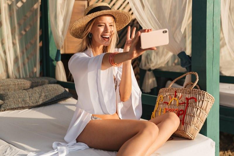 protezione solare giovane bella donna tipo misto fototipo 3 sorridente cappello paglia copricostume bianco smartphone selfie borsa estate mare
