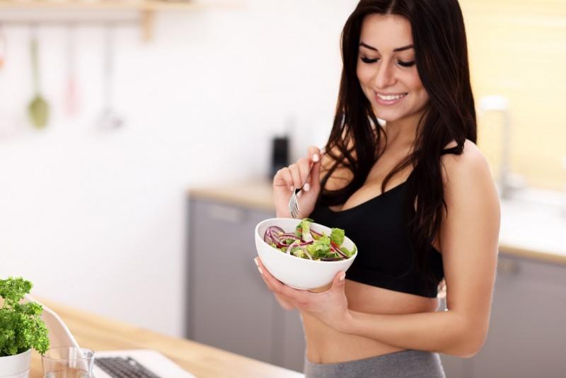 giovane bella donna mancgia insalata sana alimenazione sorriso abbigliamento fitness