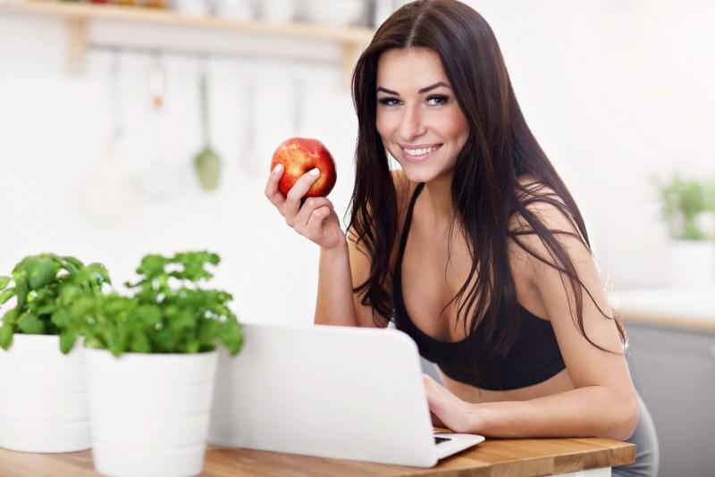 giovane bella donna mangia mela sana alimentazione guarda notebook laptop