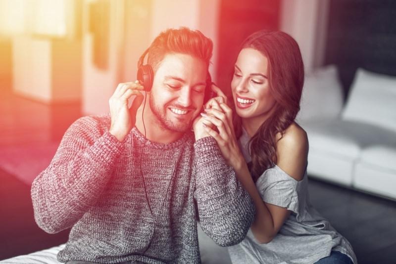 coppia innamorati lei fa ascoltare musica con cuffie a lui sorrisi