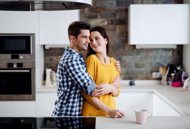 giovane coppia abbraccio complicità sorrisi serenità cucina