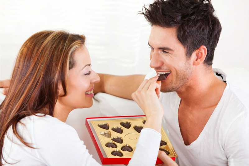 giovane coppia donna uomo mangiare cioccolato fondente afrodisiaco sorrisi