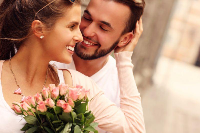 giovane coppia sorrisi uomo donna romantici bouquet mazzo fiori rose rosa