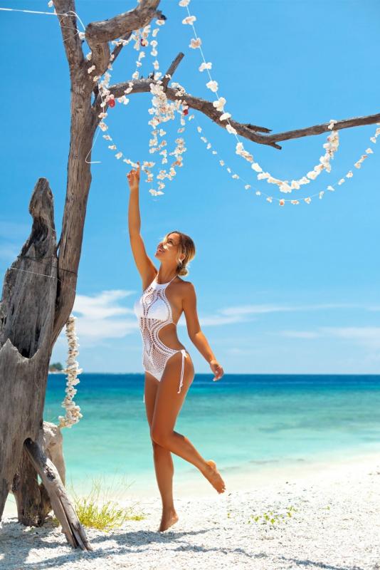 giovane donna capelli biondi bella abbronzatura pelle dorata costume uncinetto cotone bianco sole sul viso sorriso tronco albero ghirlande fiori mare estate