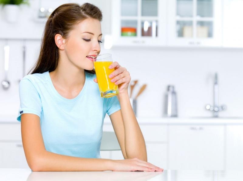 giovane bella donna beve un bicchiere con spremuta arancia