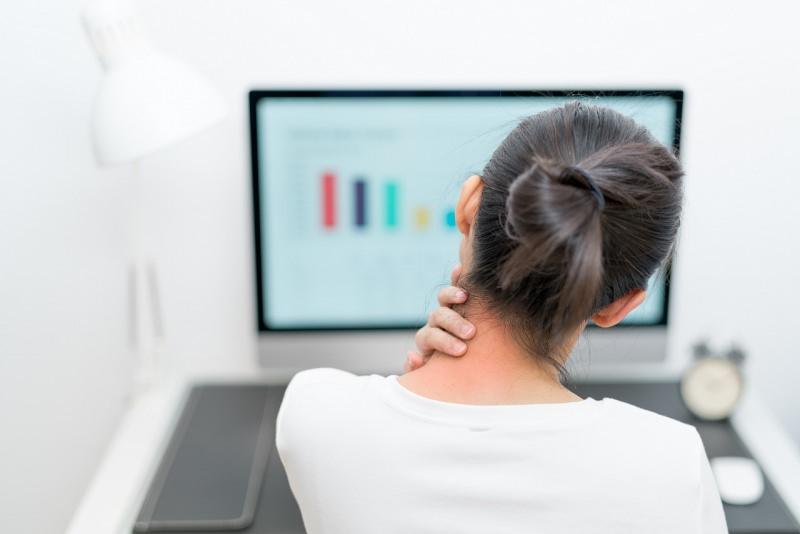 giovane donna di spalle dolore al collo cervicale infiammata cervicalgia