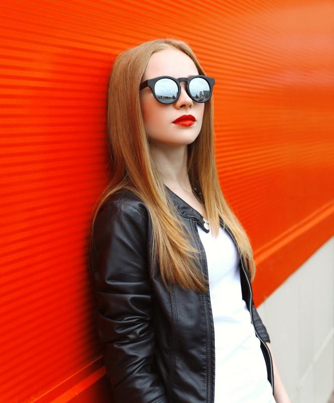 giovane e bella donna bionda occhiali da sole t-shirt bianca sotto giubbotto di pelle nero
