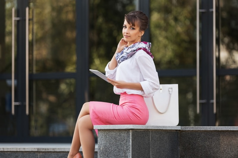 giovane e bella donna elegante panchina parco gonna a matita rosa blusa borsa bianca tablet