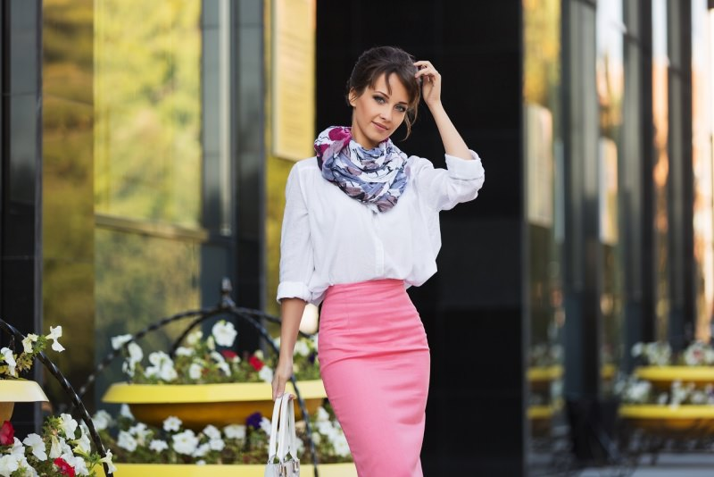 giovane e bella donna elegante al lavoro con gonna a matita rosa blusa bianca scialle