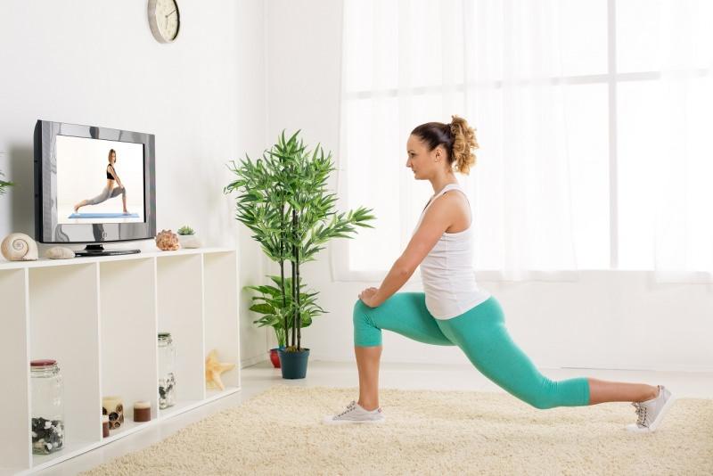 giovane donna fa stretching davanti alla tv