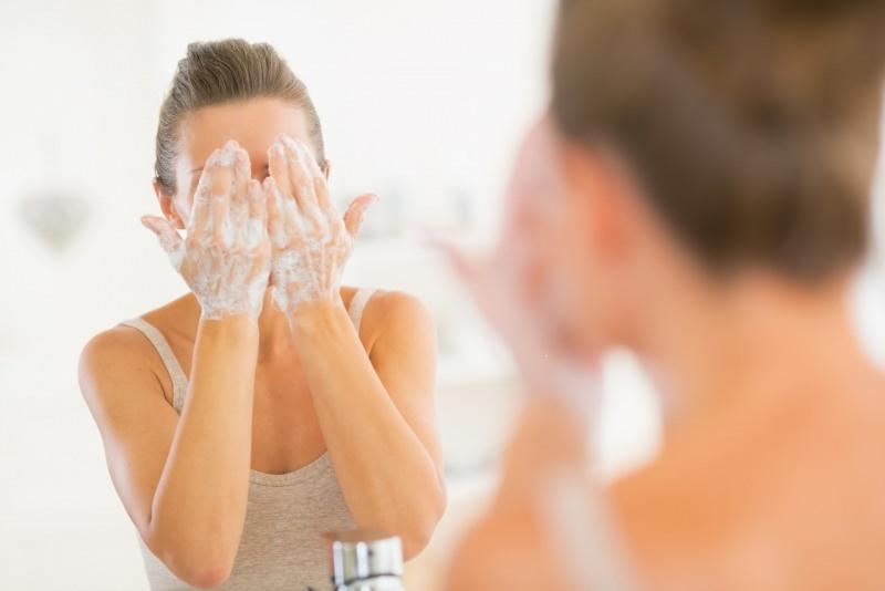 pulizia viso donna allo specchio bagno