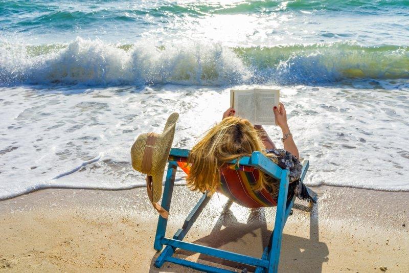 donna legge libro al mare onde sole cappello estate relax