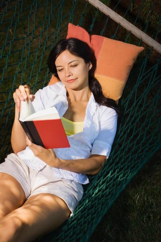 donna serena felice legge libro romanzo su amaca capelli lunghi castani relax