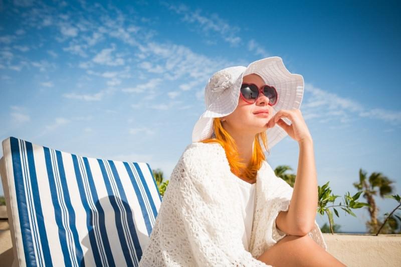 giovane bella donna capelli rossi tipo celtico fototipo 1 cappello occhiali da sole protezione solare